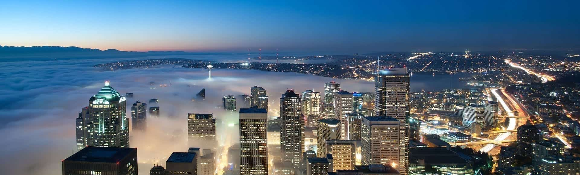 A nighttime view of downtown Seattle with its high-raise buildings partially obscured by fog