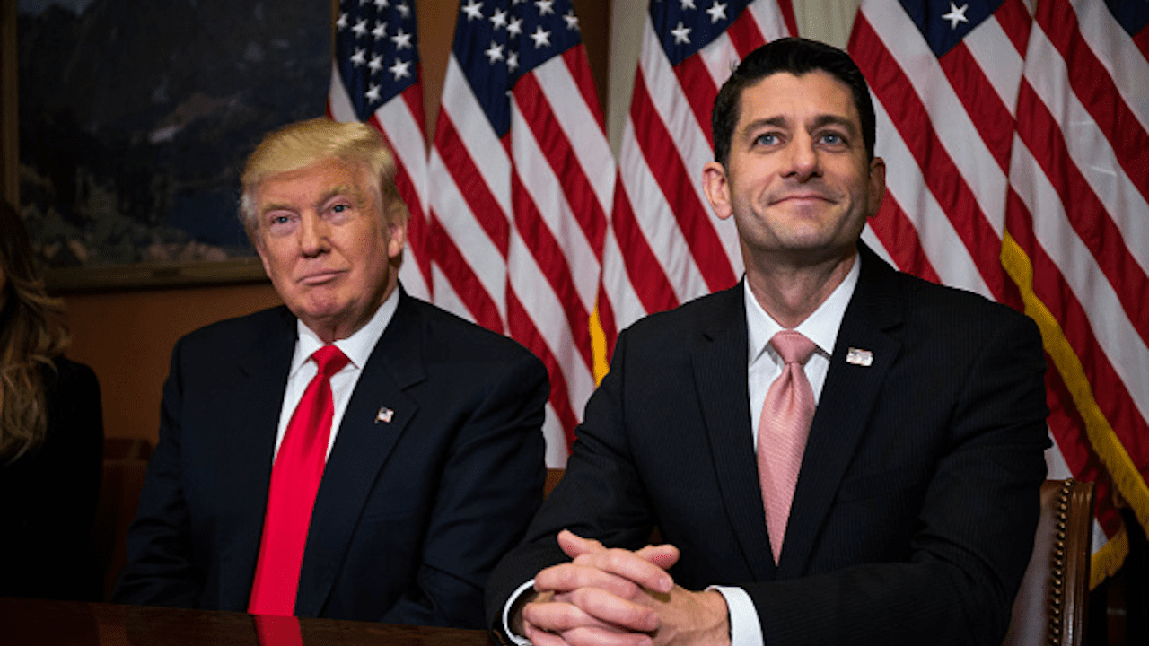 President Trump and House Speaker Paul Ryan sit side-by-side in front of a row of American flags.