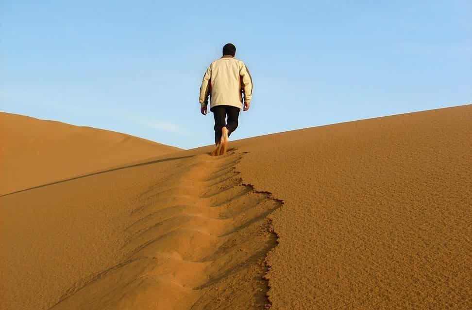 A desert guide walks away from us, his footprints blurred in the shifting sands of a dune.