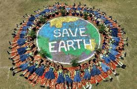 """Students lying on the ground in a circle around a globe painted on the lawn. The center of the globe says """"Save Earth."""""""