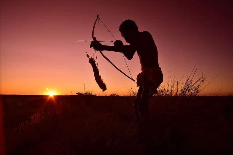 A Kalahari Bushman with bow and arrow, at sunset.