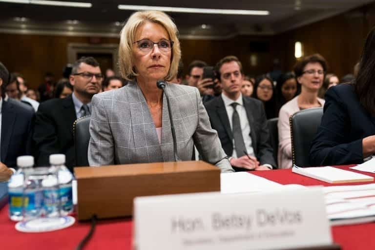 Betsy DeVos sitting at conference