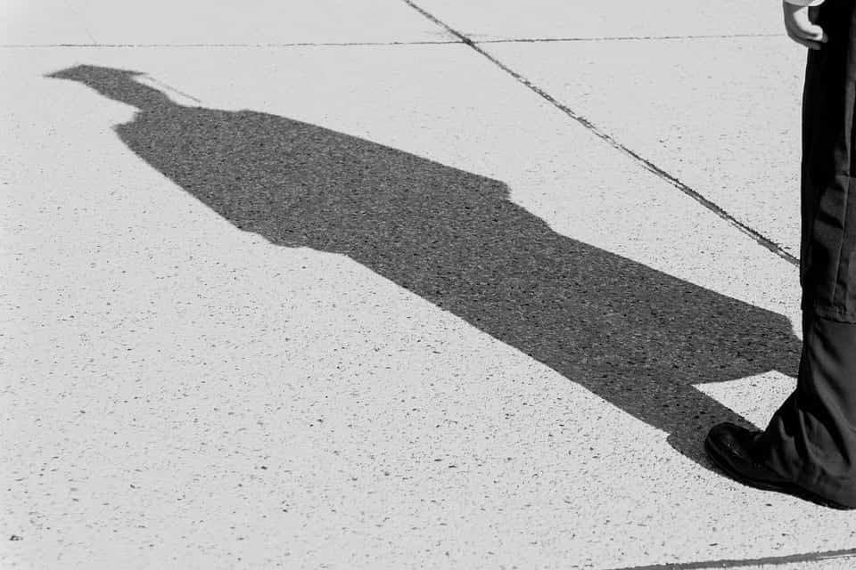 The shadow of a graduate in cap and gown falls upon the grey sidewalk.