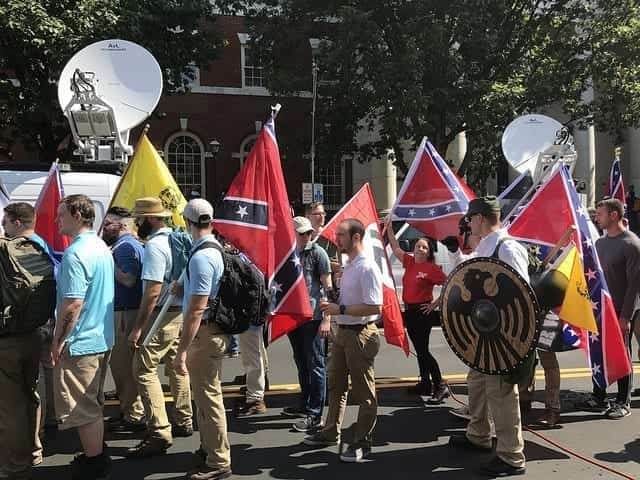 "Alt-right members preparing to enter Emancipation Park holding Nazi, Confederate, and Gadsden ""Don't Tread on Me"" flags."