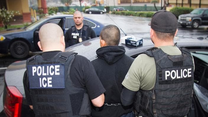 Immigrant being taken into custody by ICE agents