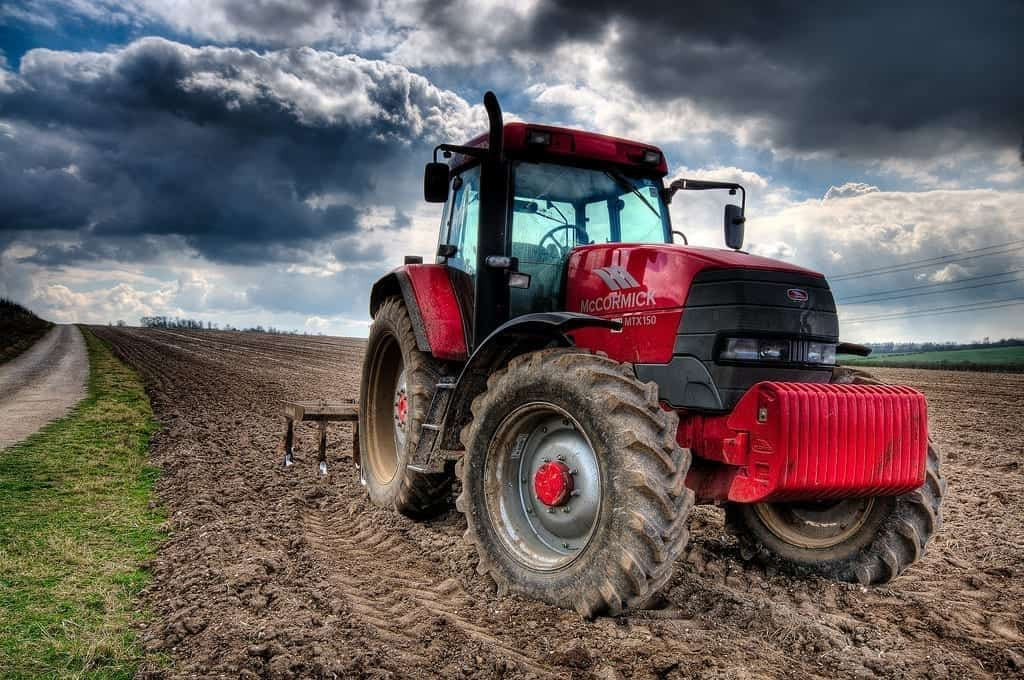 A driverless tractor sits parked in a plowed field, with ominous clouds in the background.