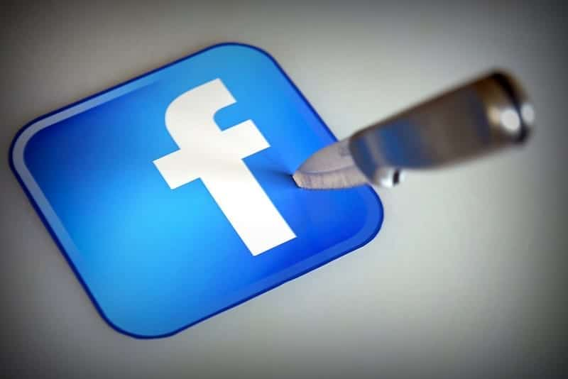 A thrown knife stabs into the Facebook logo.