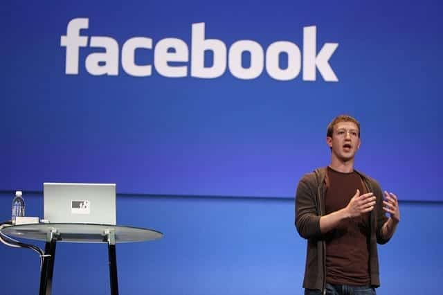 Mark Zuckerberg stands to speak in front of a blue background with the Facebook logo, alongside a small take with water and a laptop computer.