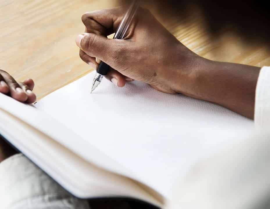 Image of a person writing in a notebook
