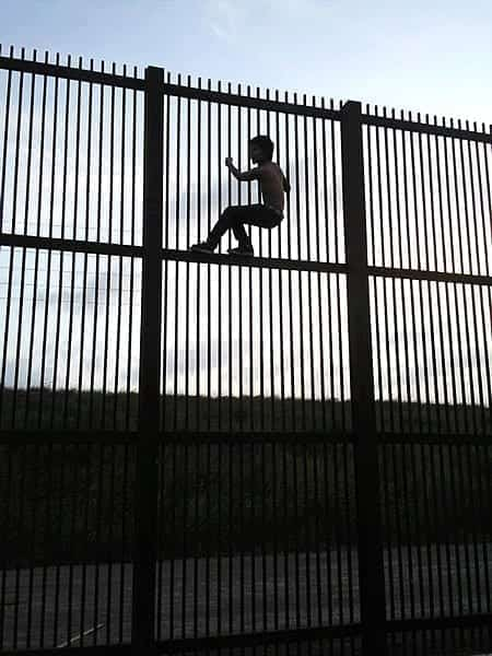 The silhouette of a child climbing a tall, slatted fence. The child is near the top.