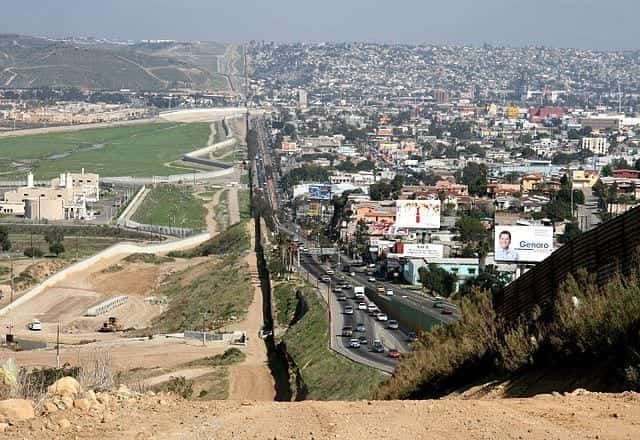 A view of the border between the U.S. and Mexico in southern California. On the Mexican side, Tijuana is full of buildings, cars, and life. On the right, San Diego seems empty in comparison.