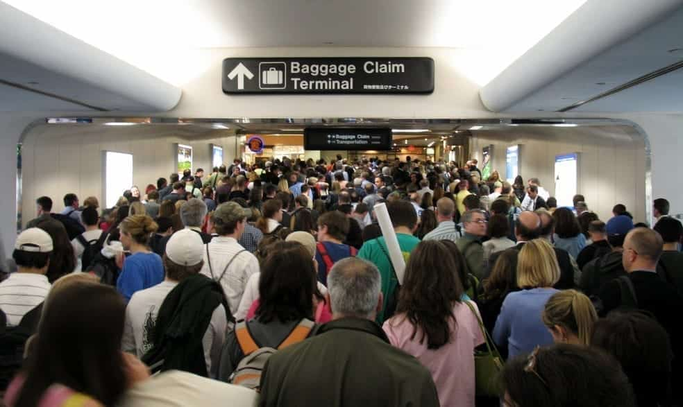 An airport hallway chock full of people heading to the baggage claim area.