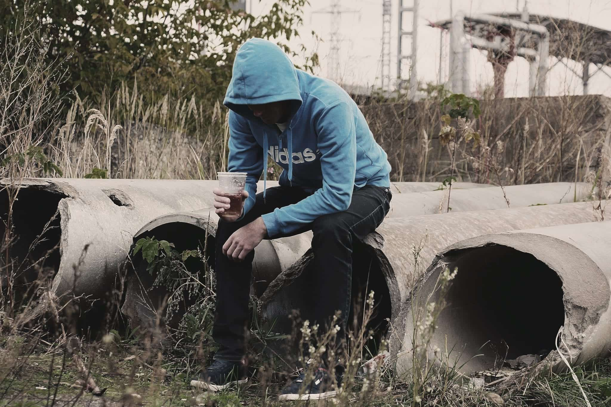 Man sitting alone in abandoned area; image via Pxhere, CC0.