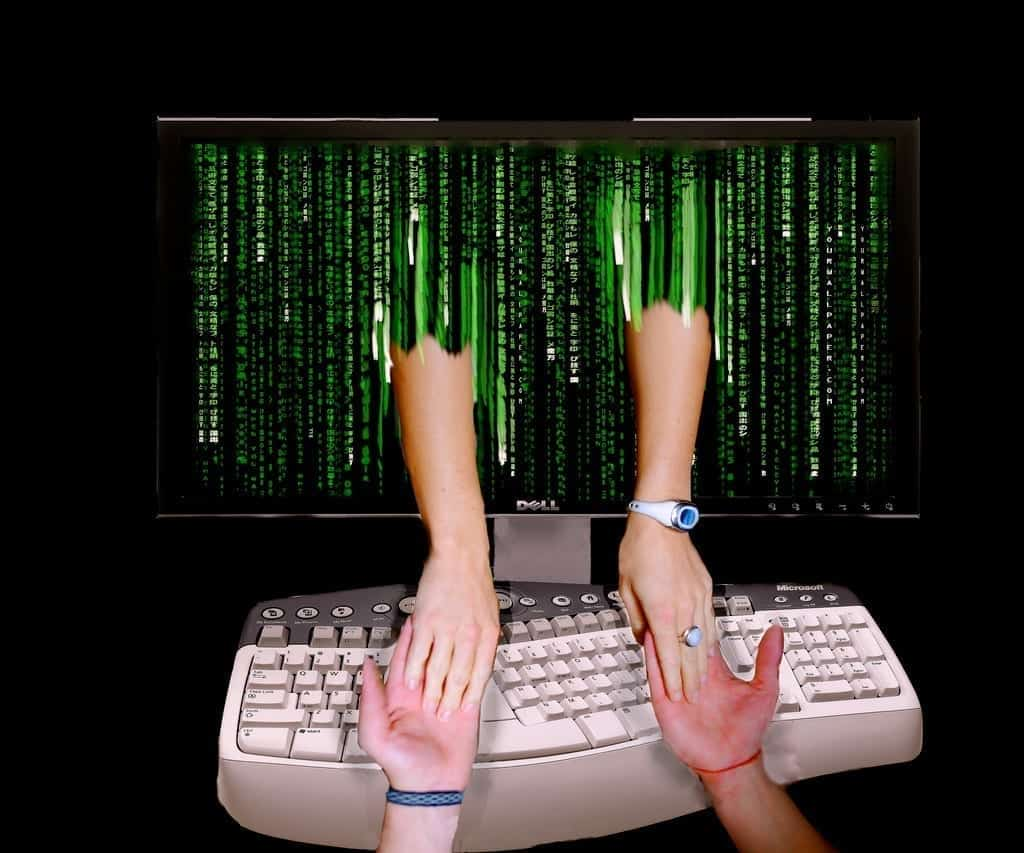 Online romance – man and woman joining hands through computer monitor; image by Don Hankins, via Flickr, CC BY 2.0, no changes.
