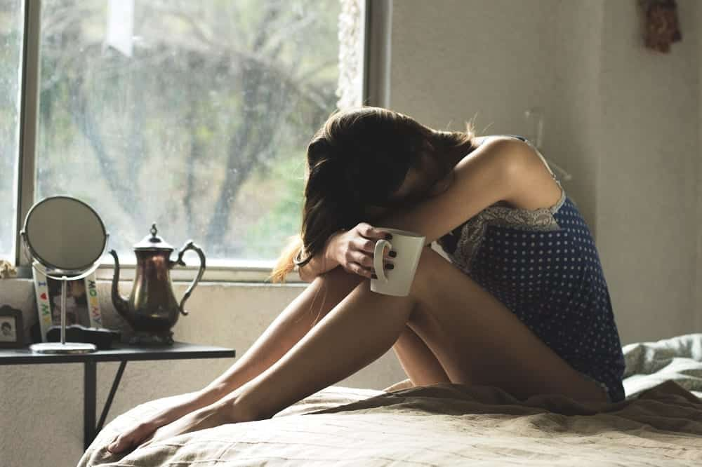 Sad woman in bed holding coffee mug with her head on her knees; image by Asdrubal luna, via Unsplash.