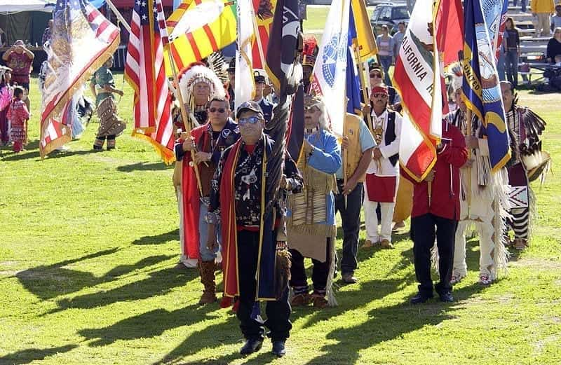 Native Americans in colorful regalia stand in loose formation, posting their colors: various flags of the United States, military branches, states and Native nations.