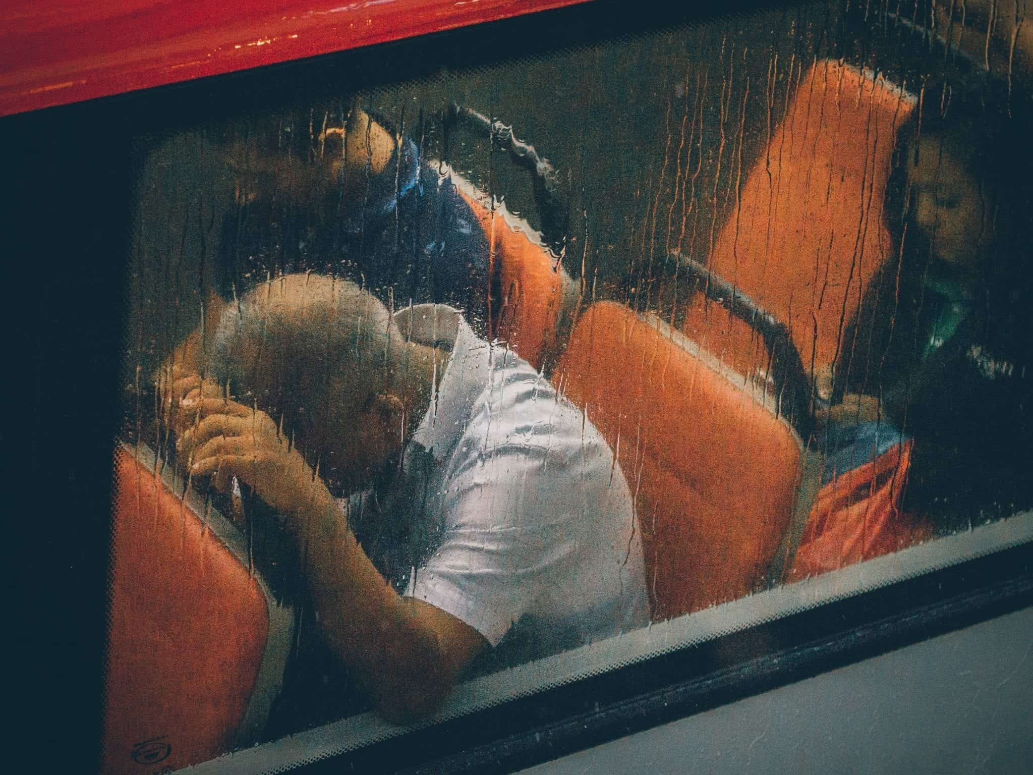 Man sleeping on train; image by Lily Banse, via Unsplash.com.