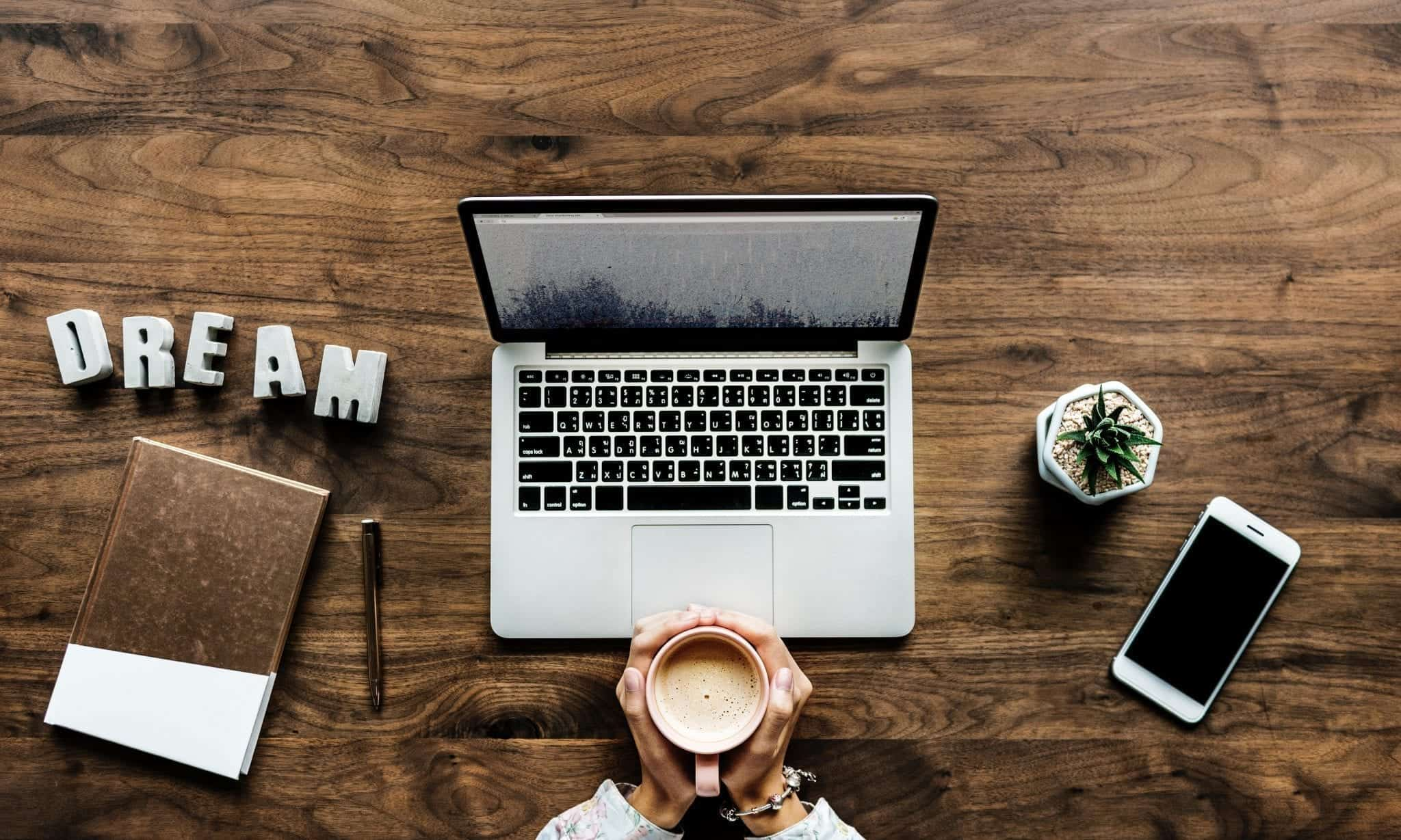 """Woman sitting at table with laptop, coffee, and a sign saying """"Dream;"""" image by Rawpixel, via Unsplash.com."""