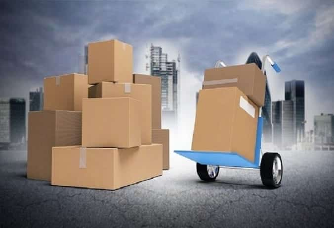Various sizes of cardboard boxes, some on a dolly; image via Shutterstock, purchased by the author.