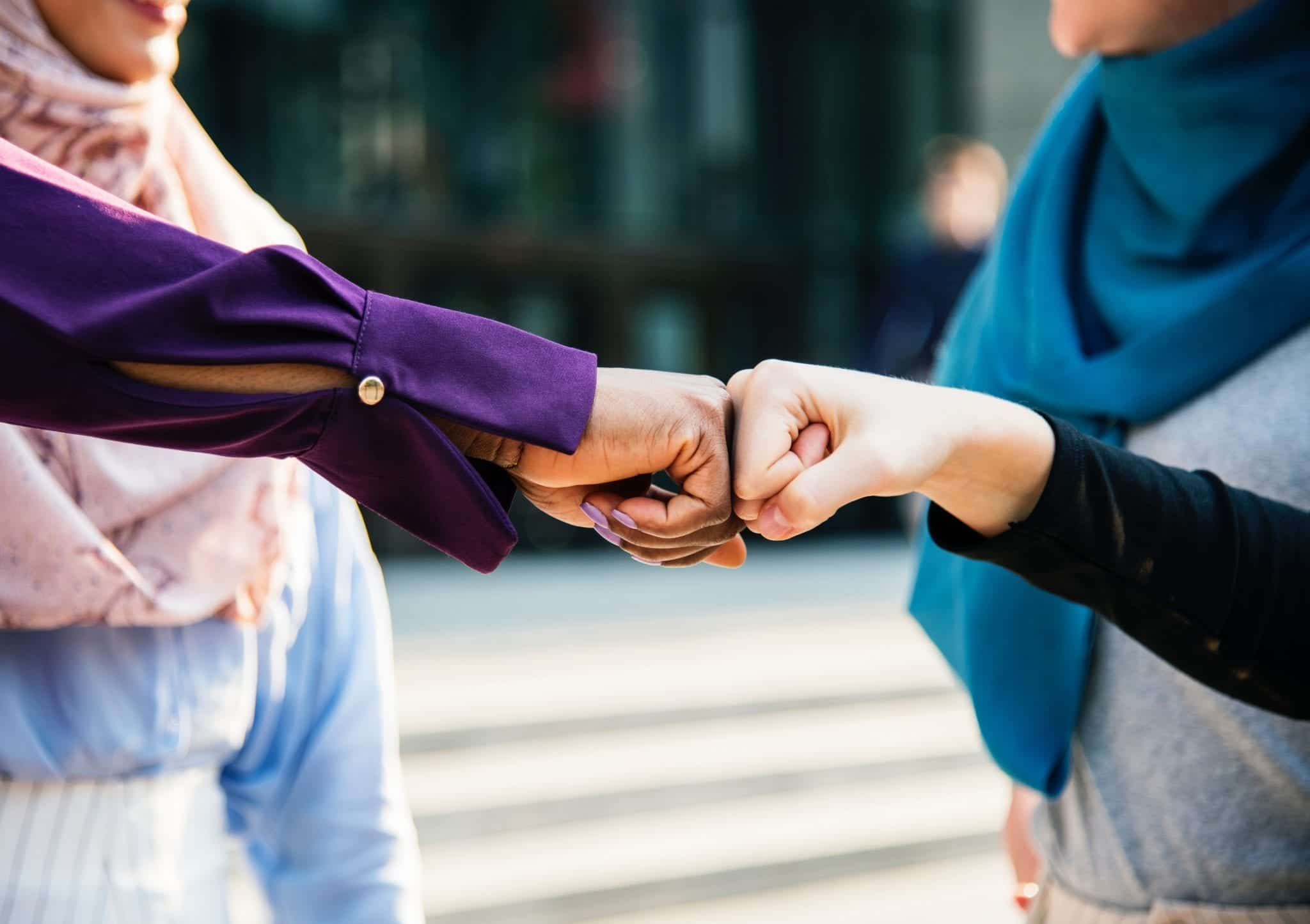 Two women bumping fists; image by Rawpixel, via Unsplash.com.
