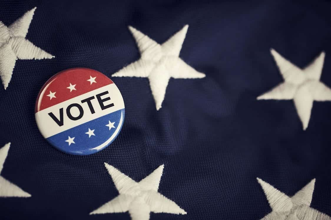 """A red, white, and blue button that says """"VOTE"""" lies atop the starry blue field of an American flag."""