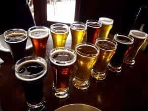 A dozen pint glasses, each filled with a different style or color of beer, sit in two rows on a restaurant table.