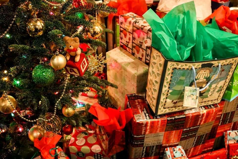 Christmas gifts in bags and boxes piled high near a festively decorated Christmas tree.