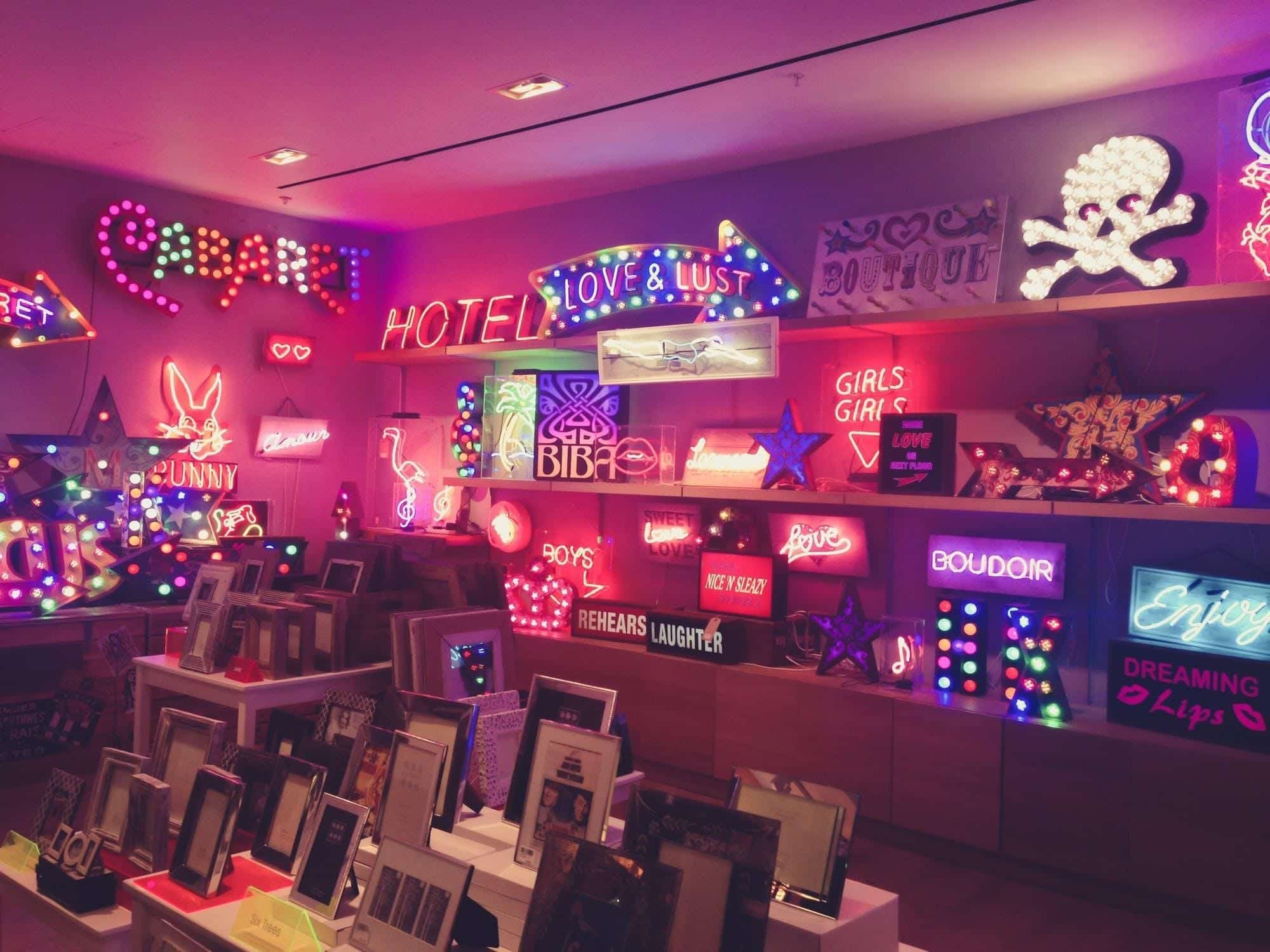 Store shelves of neon signs displaying various sayings; image by Kokil Sharma, via Pexels.com.