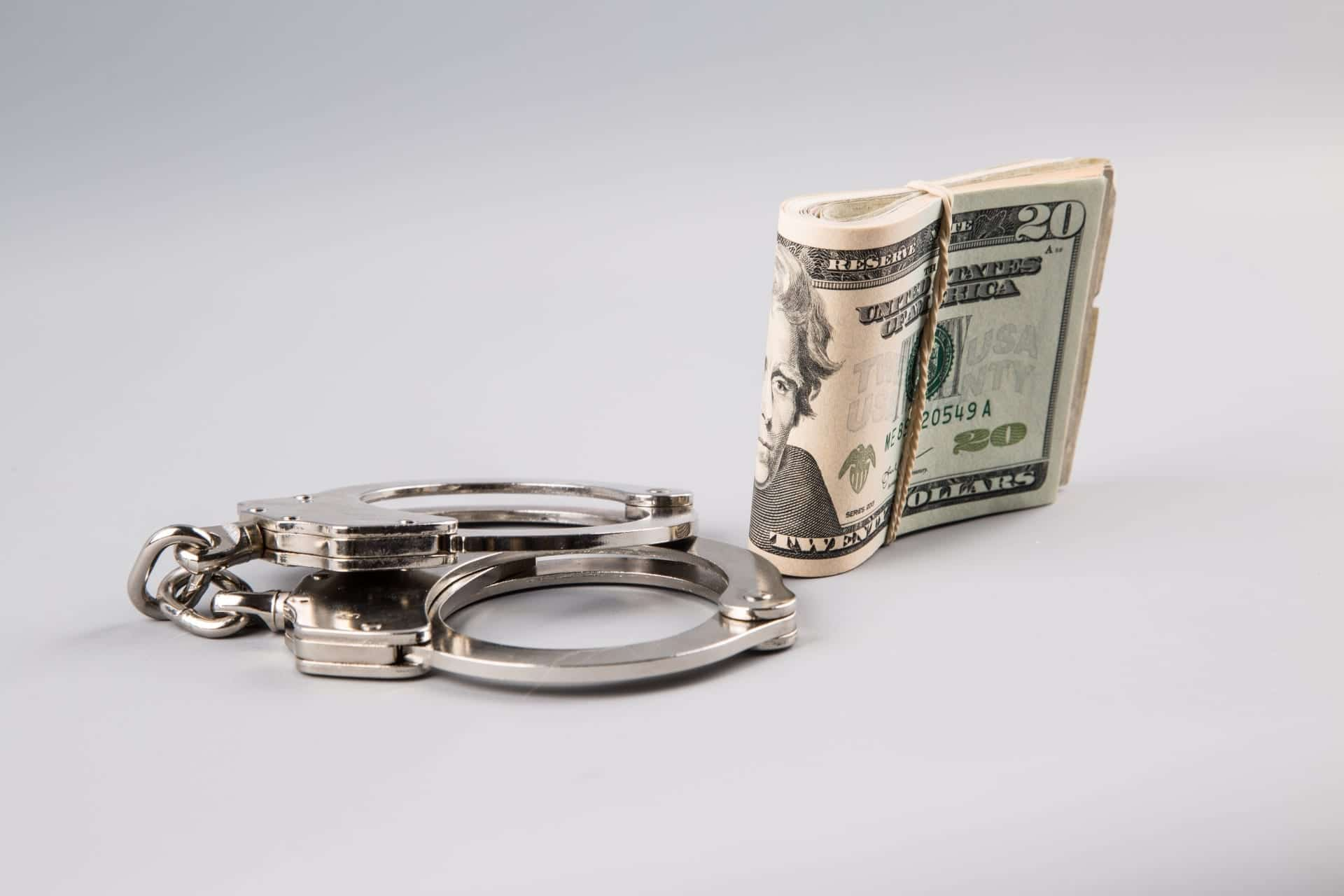 Handcuffs and money on grey background; image by George Hodan, via PublicDomainPictures.net, CC0.