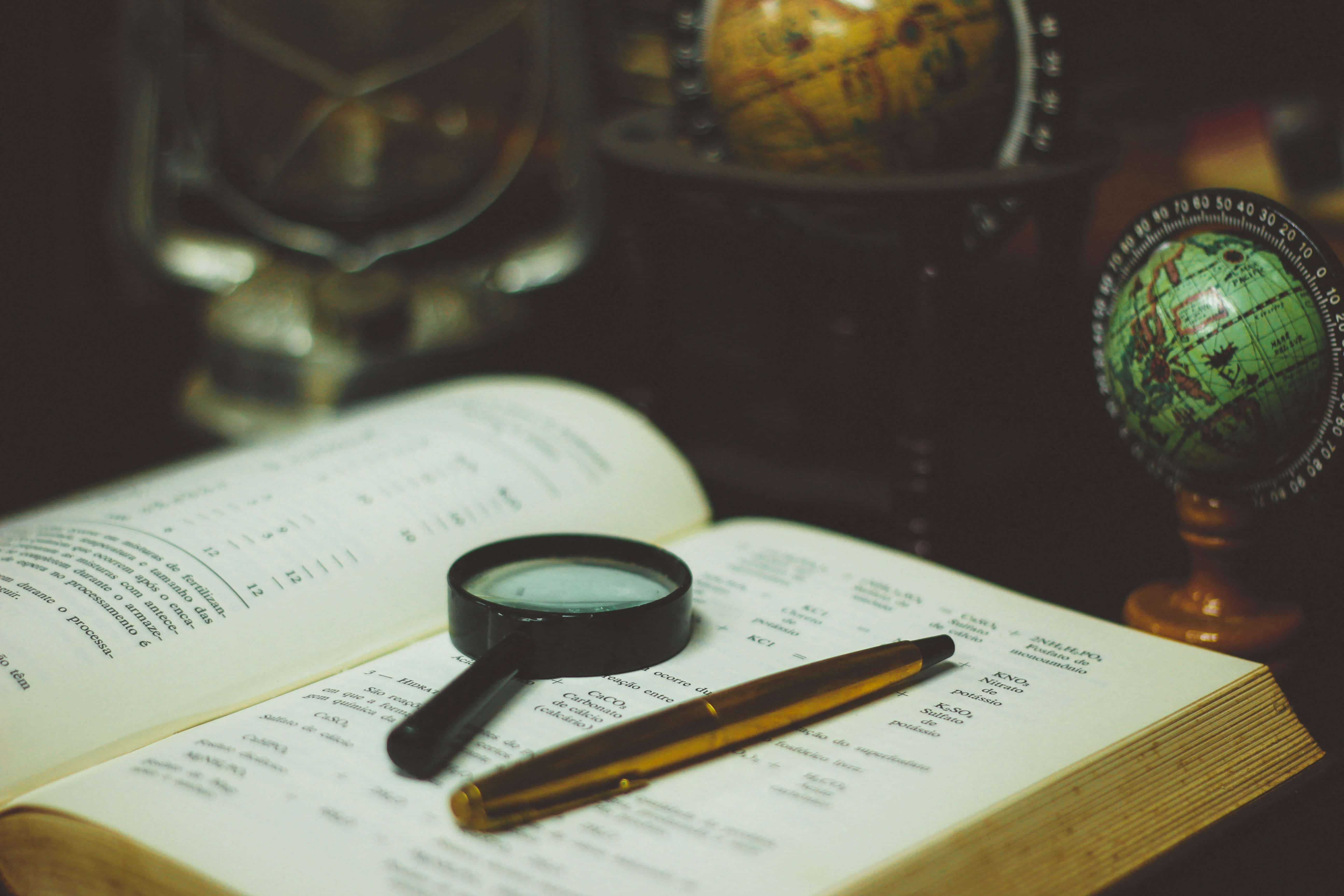 Magnifying glass and pen on book; image by João Silas, via Unsplash.com.
