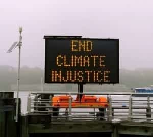 "Lighted sign saying ""End Climate Injustice."" Image by Jon Tyson, via Unsplash.com, cropped to reduce visible sky."