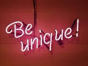"Pink neon sign on wall saying ""Be Unique."" Image via PxHere.com, CC0."
