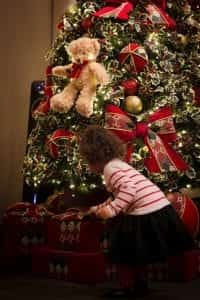 A curly haired toddler in a striped shirt explores the presents under a festively decorated Christmas tree.