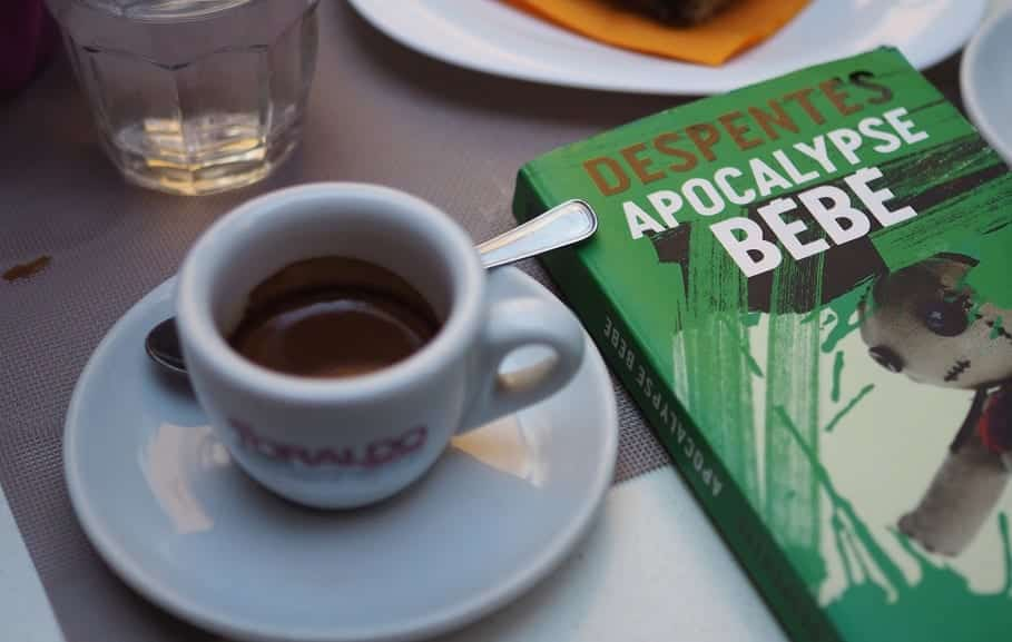 A small, white mug of black coffee on a table next to the book Apocalypse Bébé.