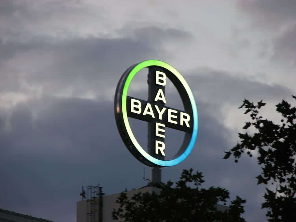 Lighted Bayer sign against a dark, cloudy sky; image by Conan, via Flickr, CC BY 2.0, no changes.