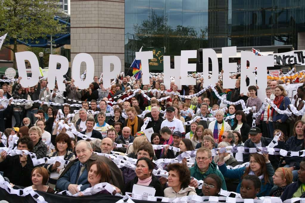 "A crowd of people, bound by paper chain links, hold up letters that spell out ""Drop The Debt."""