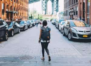 Woman wearing backpack standing on a cobblestone road; image by Brevitē, via Unsplash.com.