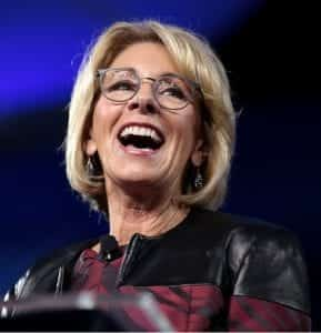 U.S. Secretary of Education Betsy DeVos, standing at a podium with a wide grin.