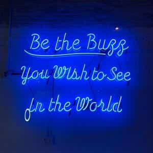 """Neon blue """"Be the buzz you wish to see in the world"""" sign; image by Tanya Santos, via Unsplash.com."""