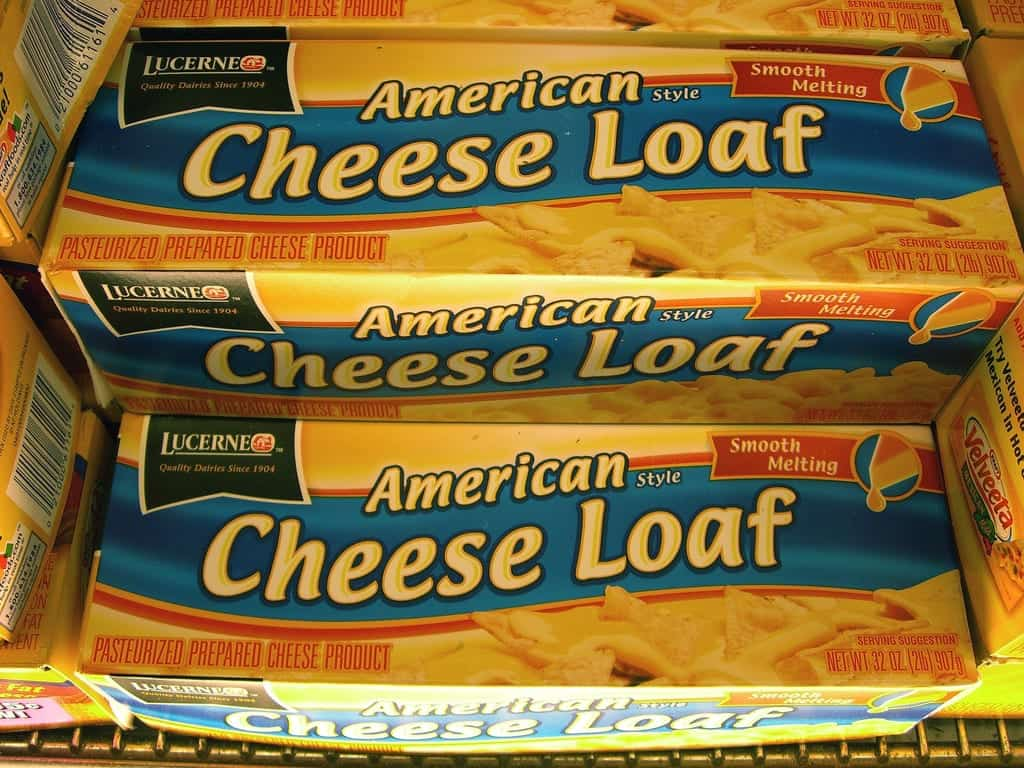 Stacked packages of Lucerne brand pasturized processed American cheese loaf food product.