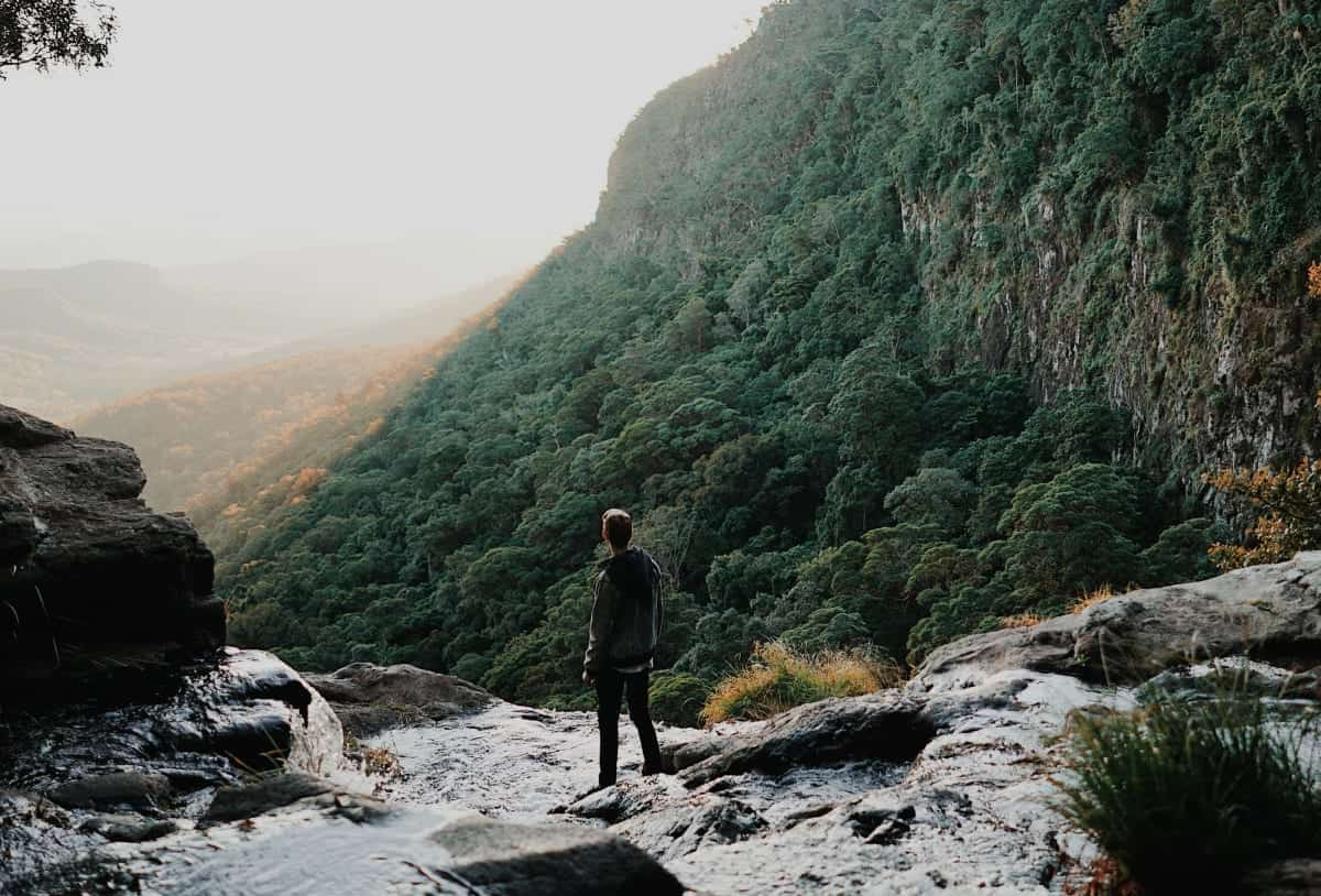 Man surrounded by hills and a stream looking at the horizon; image by Chris Fuller, via Unsplash.com.