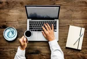 Man with laptop, cup of coffee, and journal; image by Rawpixel, via Unsplash.com.
