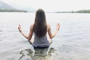 Woman in seated meditation in the water at a lakeshore; image by Audrey Hope, via Reshot.com.