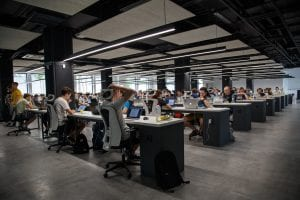 Large group of people working on computers at desks in rows; image by Alex Kotliarskyi, via Unsplash.com.