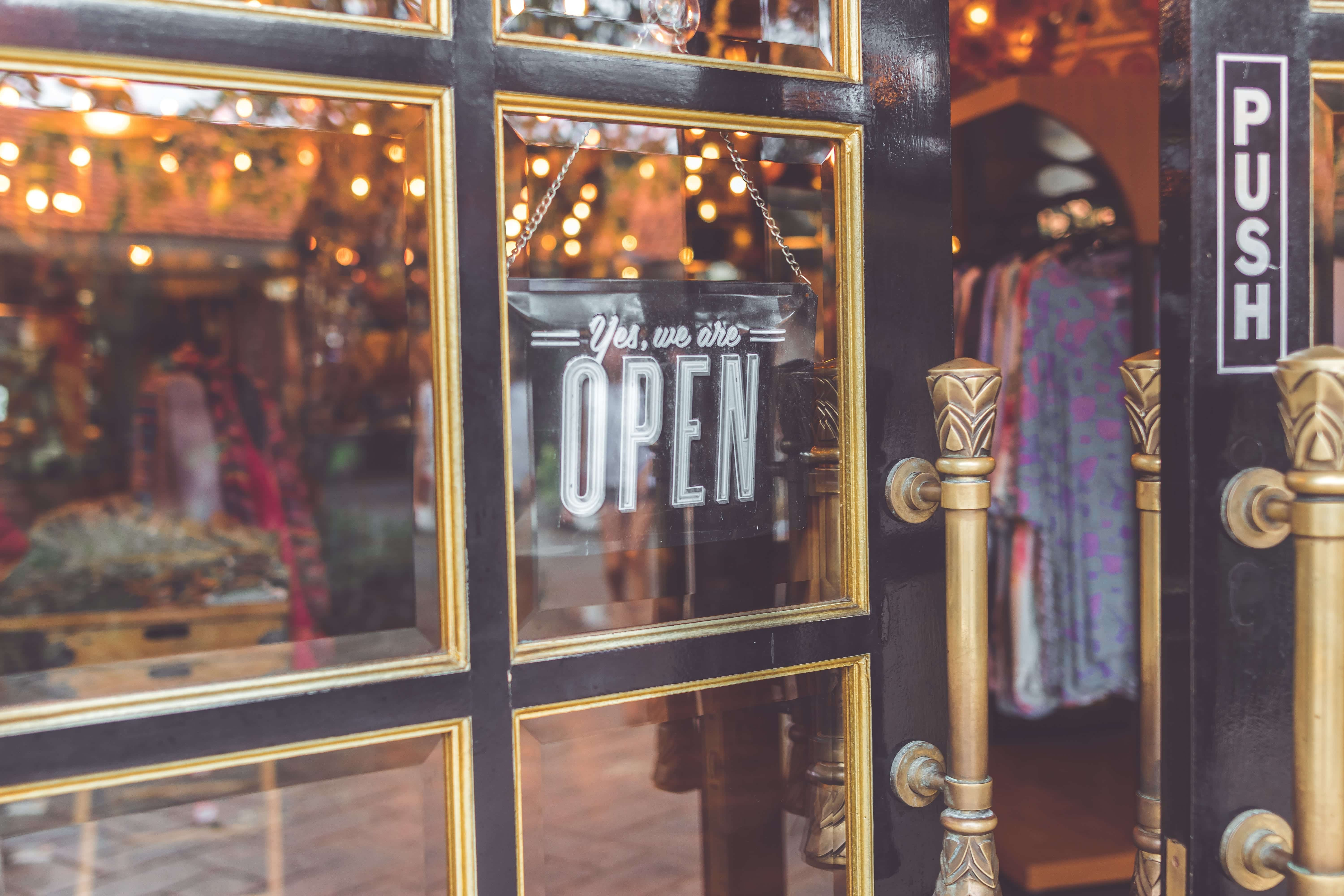"Shopfront with sign in window saying ""Yes, We Are Open;"" image by Artem Bali, via unsplash.com."