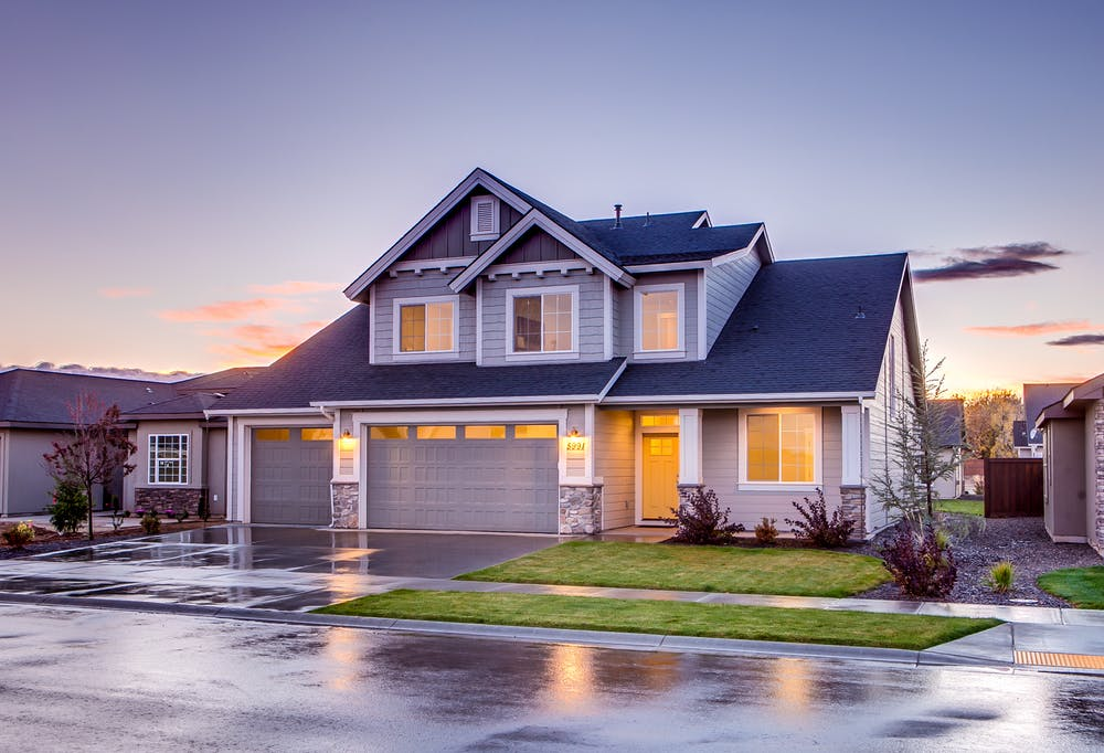 Blue and grey concrete house with attic during twilight; image by Alturas Homes, via Pexels.com.