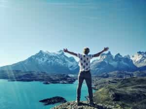 Man with hands in the air, joyfully looking at water and mountains; image by Philippe Siguret, via Unsplash.com