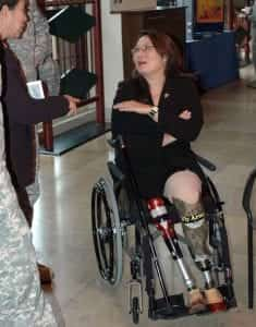 Tammy Duckworth, wearing a dark suit, with her prosthetic legs visible, sitting in her wheelchair, talking to bystanders.