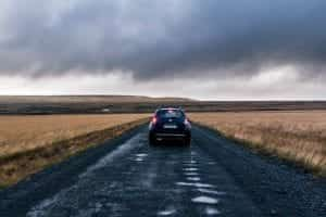 Car driving down dirt road through fields of brown grass, storm clouds in the sky; image by Kévin Langlais, via unsplash.com.