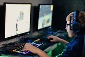 Young boy wearing headphones playing computer game; image by Alex Haney, via unsplash.com.